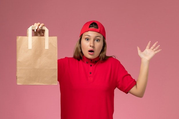 Front view female courier in red uniform and cape holding delivery paper package on the pink wall, uniform delivery service work