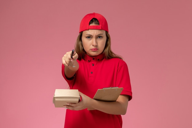 Front view female courier in red uniform and cape holding little delivery food package and notepad writing notes on pink wall, uniform delivery worker service