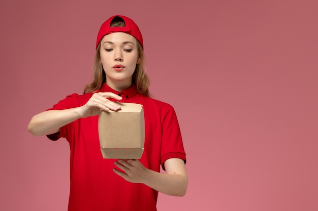 Front view female courier in red uniform and cape holding little delivery food package opening it on pink wall, worker delivery service company uniform