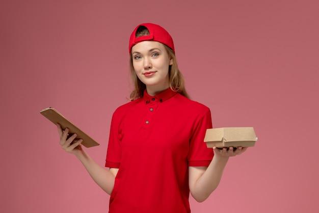 Corriere femminile di vista frontale in uniforme rossa e mantello che tiene un piccolo pacchetto di cibo per la consegna con blocco note sul muro rosa chiaro, uniforme di lavoro dell'azienda di servizi di consegna