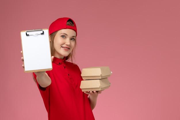 Corriere femminile di vista frontale in uniforme rossa e mantello che tiene il blocco note e piccoli pacchi di cibo di consegna sul lavoratore di consegna uniforme di servizio sfondo rosa chiaro