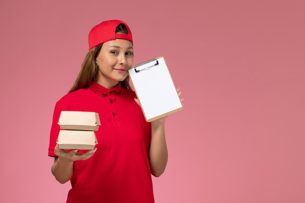 Front view female courier in red uniform and cape holding notepad and little delivery food packages on pink background uniform delivery service