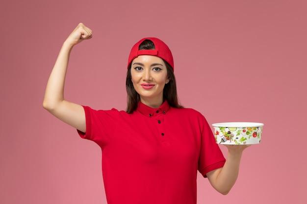 Corriere femminile di vista frontale in mantello rosso uniforme con ciotola di consegna sulle sue mani e flessione sul muro rosa chiaro, impiegato di consegna uniforme