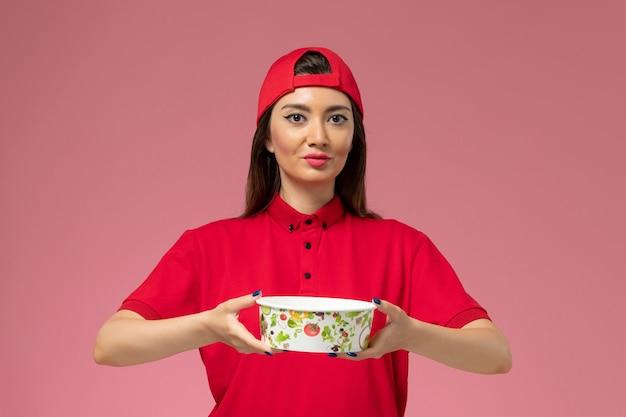 Corriere femminile di vista frontale in capo uniforme rosso con la ciotola di consegna sulle sue mani sulla parete rosa-chiaro, impiegato di consegna di servizio di lavoro di lavoro