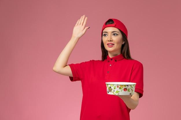 Corriere femminile di vista frontale in capo uniforme rosso con la ciotola di consegna sulle sue mani che fluttuano sulla parete rosa chiaro, impiegato di consegna di servizio
