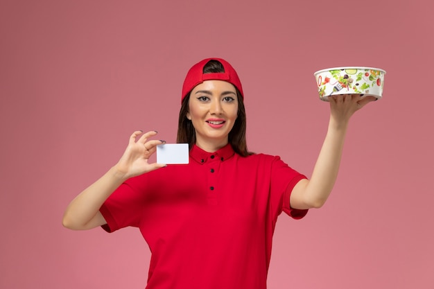 Front view female courier in red uniform cape with delivery bowl and white card on her hands on light pink wall, uniform delivery employee job