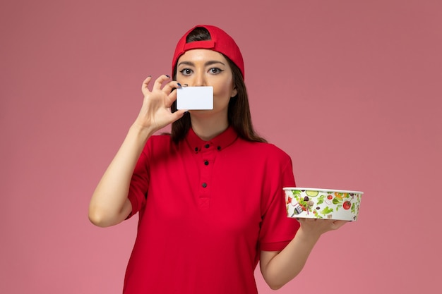 Front view female courier in red uniform cape with delivery bowl and white card on her hands on light pink wall, uniform delivery employee work job