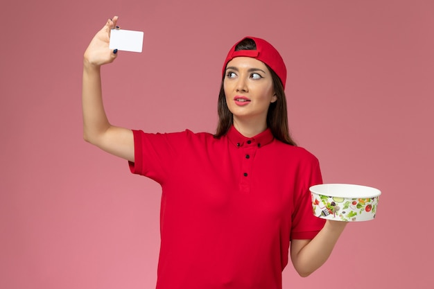 Front view female courier in red uniform cape with delivery bowl and white card on her hands on light pink wall, uniform delivery employee worker