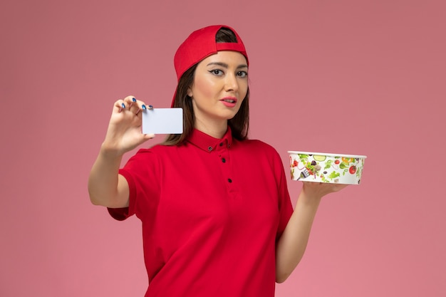 Front view female courier in red uniform cape with delivery bowl and white card on her hands on light pink wall, uniform job delivery employee