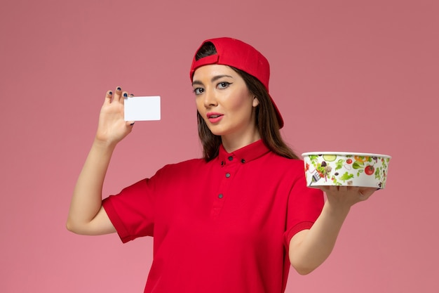 Front view female courier in red uniform cape with delivery bowl and white card on her hands on light pink wall, work uniform delivery employee