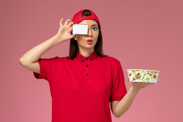 Front view female courier in red uniform cape with delivery bowl and white card on her hands on light pink wall, worker uniform delivery employee