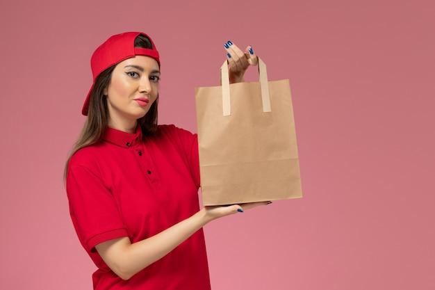 Corriere femminile di vista frontale in mantello rosso uniforme con pacco di carta di consegna sulle sue mani sul muro rosa chiaro, lavoro dipendente di consegna uniforme