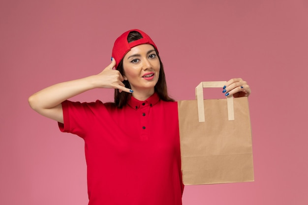 Front view female courier in red uniform cape with delivery paper package on her hands smiling on pink wall, uniform delivery employee