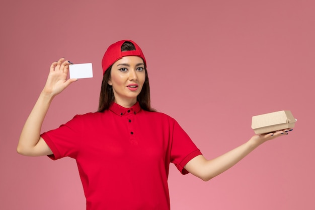 Front view female courier in red uniform cape with little delivery food package and card on her hands on light-pink wall, service delivery employee job