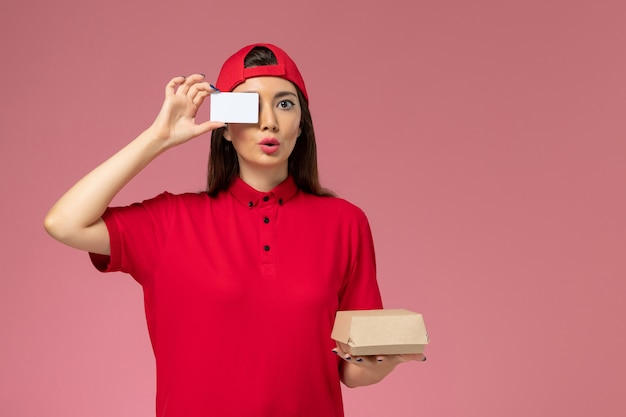 Front view female courier in red uniform cape with little delivery food package and card on her hands on light-pink wall, service delivery employee work