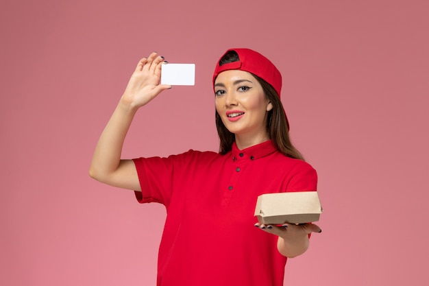 Front view female courier in red uniform cape with little delivery food package and card on her hands on light-pink wall, service delivery employee