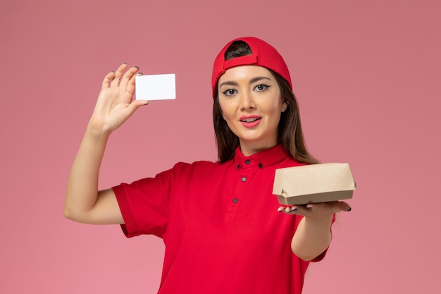 Front view female courier in red uniform cape with little delivery food package and card on her hands on light-pink wall, service work delivery employee