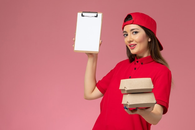 Front view female courier in red uniform cape with notepad and little delivery food packages on her hands on light-pink wall, work service delivery employee