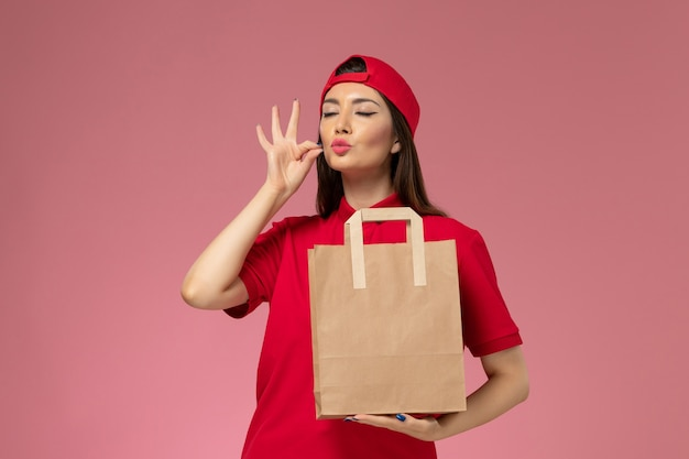Front view female courier in red uniform cape with paper delivery package on her hands on light pink wall, uniform delivery employee work job