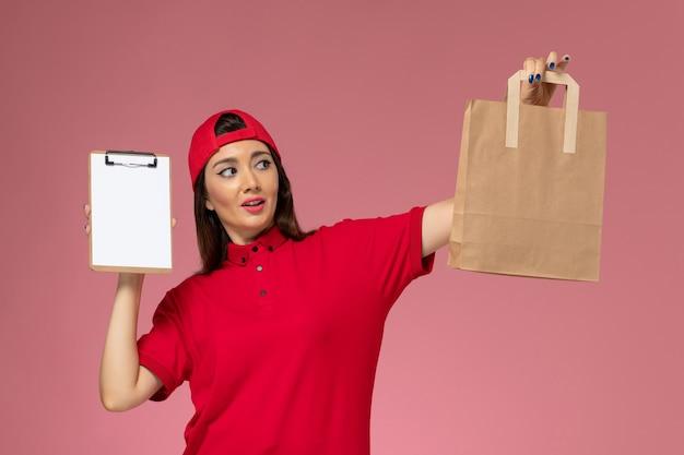 Corriere femminile di vista frontale in mantello rosso uniforme con pacco di consegna di carta e blocco note sulle mani sul muro rosa chiaro, impiegato di consegna uniforme di lavoro