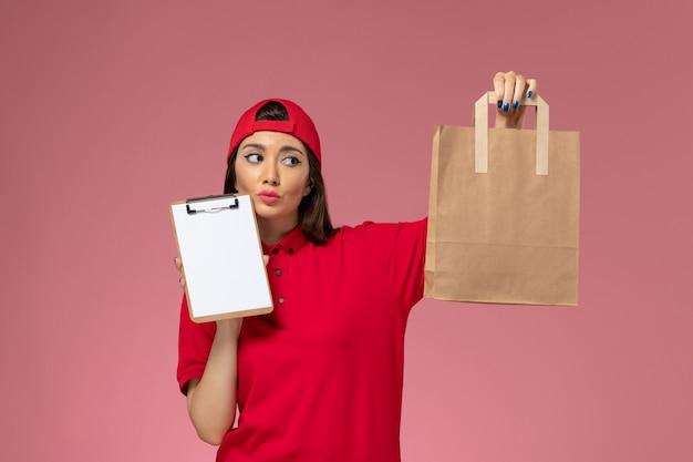 Corriere femminile di vista frontale in mantello rosso uniforme con pacco di consegna di carta e blocco note pensando sulle sue mani sull'impiegato di consegna uniforme da scrivania rosa