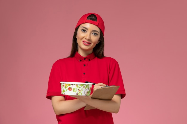 Front view female courier in red uniform cape with round delivery bowl notepad on her hands writing notes on light pink wall, uniform delivery employee job
