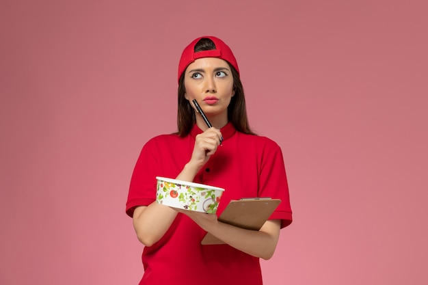 Front view female courier in red uniform cape with round delivery bowl notepad on her hands writing notes on light pink wall, uniform delivery employee worker