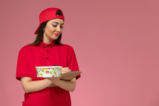 Front view female courier in red uniform cape with round delivery bowl notepad on her hands writing notes on light pink wall, uniform delivery employee