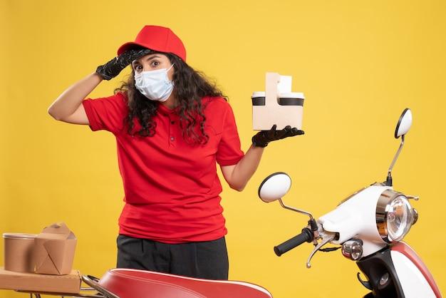 Corriere femminile di vista frontale in uniforme rossa che tiene tazze di caffè su fondo giallo servizio di covid-lavoro di consegna del lavoratore