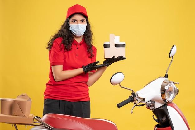 Corriere femminile vista frontale in uniforme rossa che tiene tazze di caffè su sfondo giallo consegna lavoratore covid- servizio uniforme di lavoro pandemico