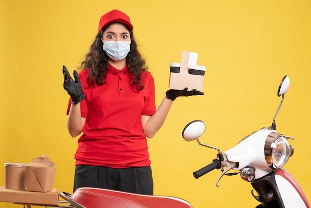 Corriere femminile vista frontale in uniforme rossa che tiene tazze di caffè su sfondo giallo consegna del lavoratore covid- divisa da lavoro pandemica