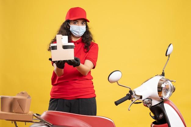 Corriere femminile vista frontale in uniforme rossa che tiene caffè su sfondo giallo consegna covid- servizio uniforme lavoro pandemico