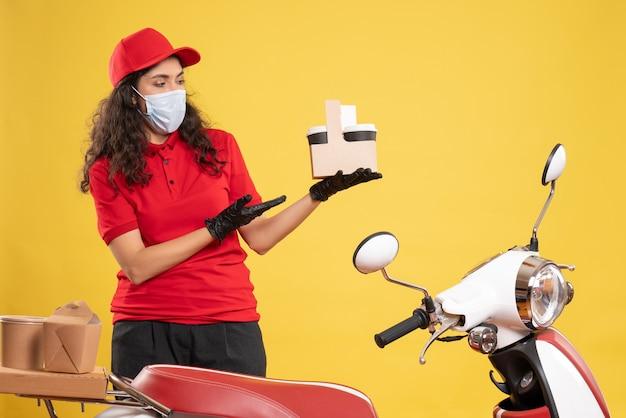 Corriere femminile vista frontale in uniforme rossa che tiene caffè su sfondo giallo consegna del lavoratore covid- servizio pandemico uniforme del lavoro