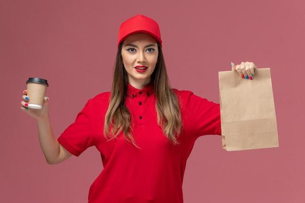 Corriere femminile di vista frontale in uniforme rossa che tiene la tazza di caffè di consegna e il pacchetto dell'alimento sul lavoro dell'uniforme di consegna di servizio del fondo rosa
