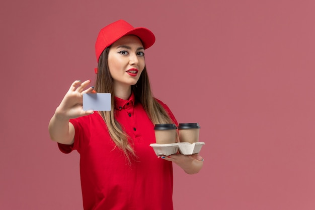 Front view female courier in red uniform holding delivery coffee cups and card posing on pink background service job delivery uniform
