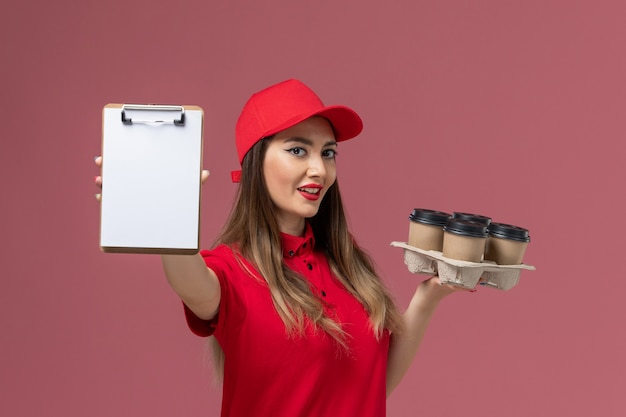 Front view female courier in red uniform holding delivery coffee cups notepad on the pink background service delivery company job uniform