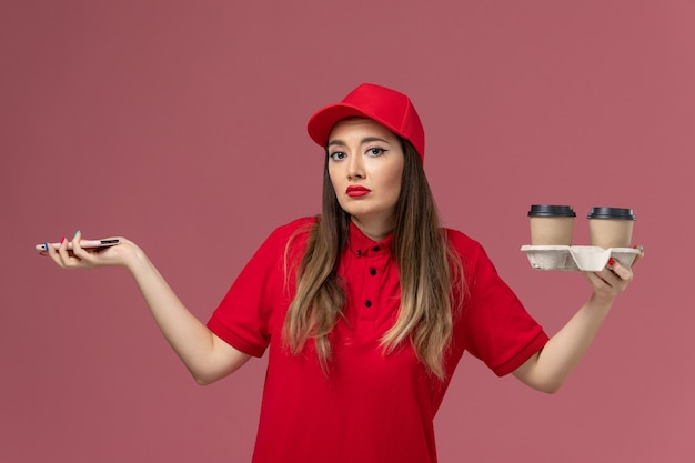 Front view female courier in red uniform holding delivery coffee cups and smartphone on light-pink background worker job service delivery uniform