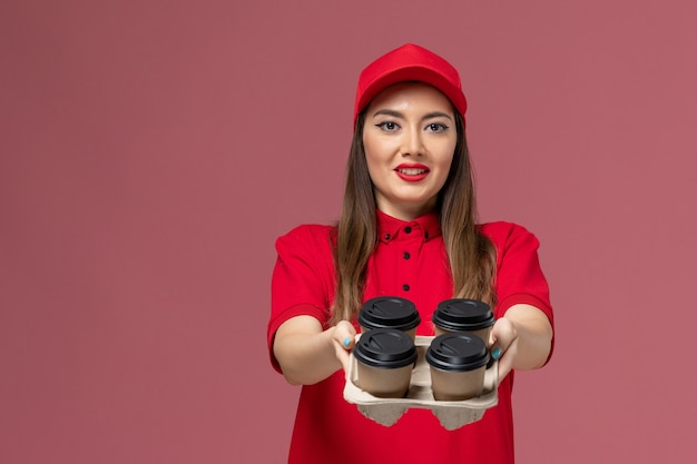 Front view female courier in red uniform holding delivery coffee cups and smartphone on the pink desk job service delivery uniform
