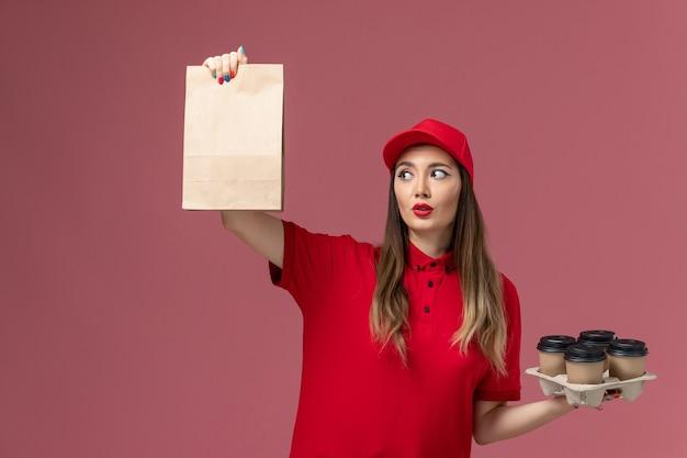 Corriere femminile di vista frontale in uniforme rossa che tiene le tazze di caffè di consegna con il pacchetto dell'alimento sull'uniforme di lavoro di consegna del servizio di sfondo rosa chiaro