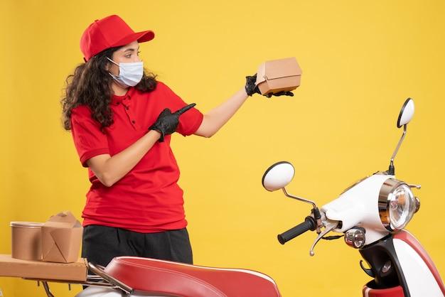 Corriere femminile vista frontale in uniforme rossa che tiene un piccolo pacchetto di cibo su sfondo giallo lavoratore uniforme di consegna del servizio di lavoro covid