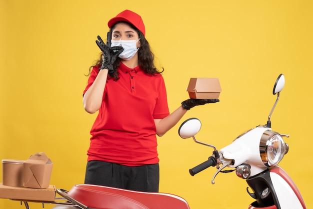 Corriere femminile vista frontale in uniforme rossa che tiene un piccolo pacchetto di cibo su sfondo giallo consegna covid-uniforme da lavoro pandemia di lavoratore