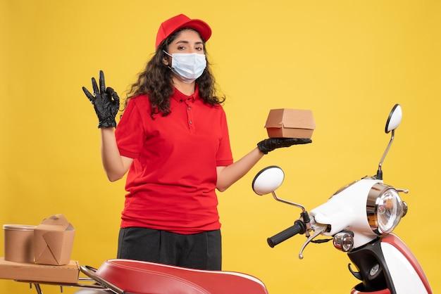 Corriere femminile vista frontale in uniforme rossa che tiene un piccolo pacchetto di cibo su sfondo giallo consegna covid- servizio uniforme pandemia di lavoratore
