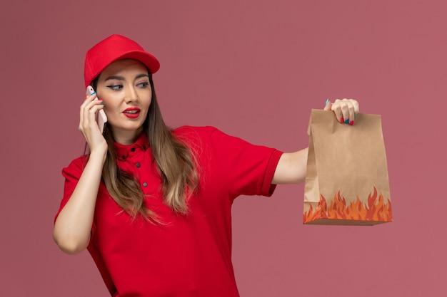 Corriere femminile di vista frontale in uniforme rossa che tiene il telefono e il pacchetto di cibo su sfondo rosa lavoratore azienda uniforme di consegna del servizio