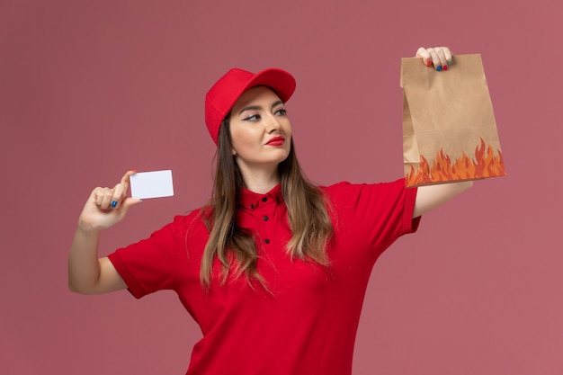 Front view female courier in red uniform holding white card and food package on the pink background service delivery uniform company