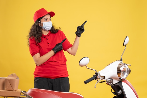 Front view female courier in red uniform and mask on yellow background covid- job delivery uniform worker pandemic