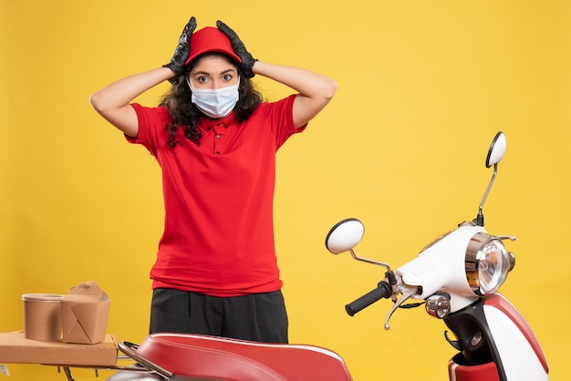 Front view female courier in red uniform and mask on yellow background covid- job service delivery uniform worker pandemic