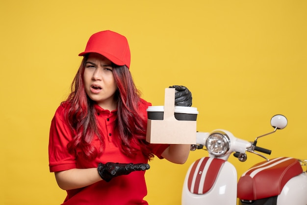 Front view of female courier in red uniform with coffee confused on yellow wall