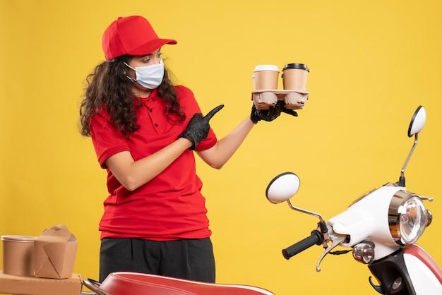 Vista frontale corriere femminile in uniforme rossa con tazze di caffè su sfondo giallo consegna covid- virus del servizio uniforme di lavoro pandemico