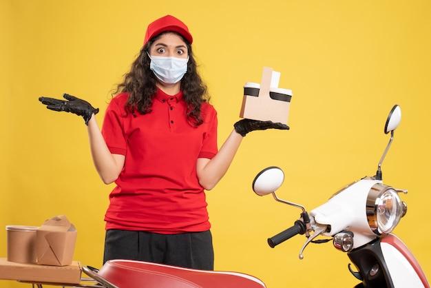 Corriere femminile vista frontale in uniforme rossa con tazze di caffè su sfondo giallo consegna del lavoratore covid- virus del servizio uniforme di lavoro pandemico
