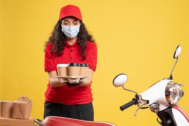 Corriere femminile vista frontale in uniforme rossa con tazze di caffè su sfondo giallo consegna lavoratore covid- servizio pandemico uniforme